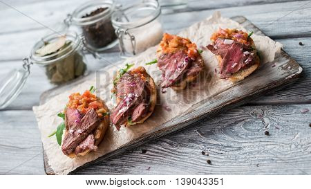 Sandwiches with meat. Mixture of cooked vegetables. Chopped onion on bruschetta. Juicy veal and fresh arugula.