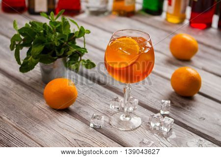 Wineglass with orange cocktail. Mint in small bucket. Aperol spritz with orange slice. Relax and enjoy your drink.