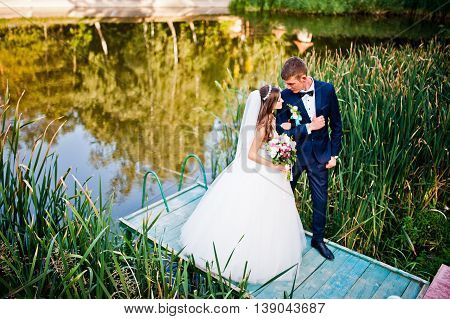 Wedding Couple Stay On Pier Of Lake With Reeds