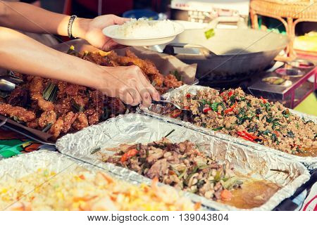 cooking, asian kitchen, sale and food concept - close up of hands with wok at street market