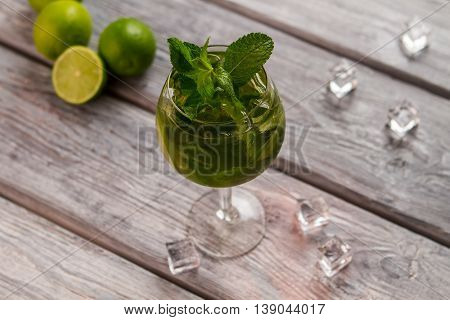 Wineglass with beverage and limes. Cocktail glass on wooden background. Correct recipe of hugo drink. Aroma of mint.
