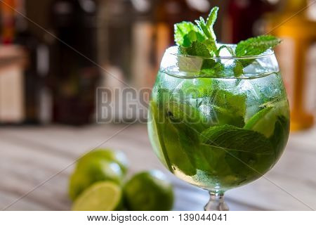 Green leaves in cocktail glass. Beverage with ice. Enjoy fresh drink. Hugo with mint and lime.