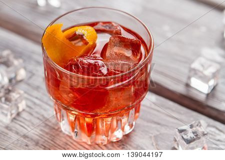 Glass with dark orange drink. Lemon peel and ice cubes. Negroni cocktail is ready. Recipe of beverage with bitter.