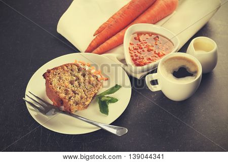 Delicious slice of carrot cake with mint on plate