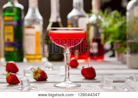 Red beverage in a glass. Ice cubes and strawberries. Refreshment after hard day. Clover club cocktail with juice.