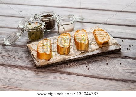 Liquid pours on baguette slice. Jar with whole pepper. How to prepare italian snack. Grilled bread and olive oil.