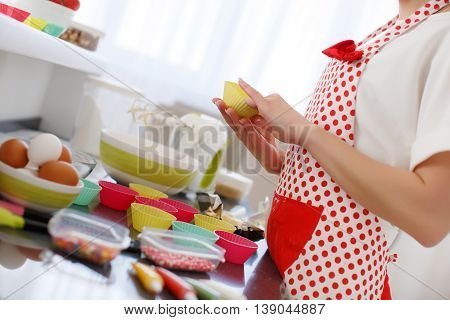 Young beautiful woman dressed in a white shirt and white red polka dot pinafore,engaged in the bright kitchen, preparing dough for baking in a colorful silicone forms