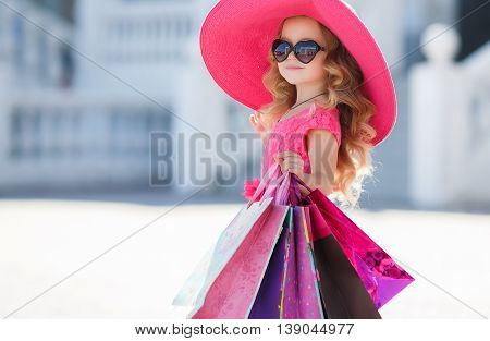 Beautiful little girl with blond long curly hair, in a pink straw hat with large brim,sun glasses with glass in the form of hearts,in a pink dress with a bunch of colored shopping bags,posing near a supermarket