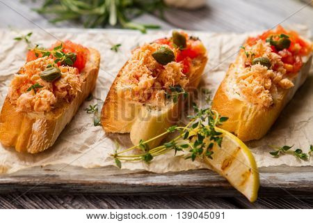 Toasts with fish meat. Green herb and capers. Freshly cooked bruschetta with salmon. Great food from organic ingredients.