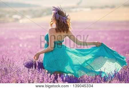 Happy pregnant brunette woman with long curly hair,large belly,dressed in a long dress turquoise,a hand holding a basket of flowers ,on her head is a wreath of field of lavender,picking flowers on a summer meadow mountain lavender