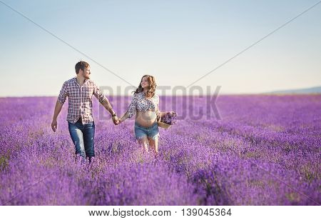 Young man and woman spend time in a flowering lavender field fragrant lavender,a pregnant woman,brunette with long curly hair ,wearing a light shirt,holding a basket of flowers lavender and a man, dark-haired man in a plaid shirt,the young family