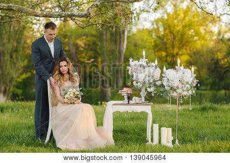 Happy young couple in love,bride and groom,blonde woman and man in wedding attire,withdrew to a green summer meadow at sunset,wedding bouquet,white table,the bride sits on a white chair,candles and French almond cakes,the romantic wedding moments