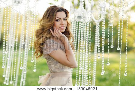 Young beautiful bride blonde woman with long curly hair, brown eyes and long black eyelashes, beautiful wedding dress beige color, posing standing at summer green park against a background illumination the glass of rain at sunset