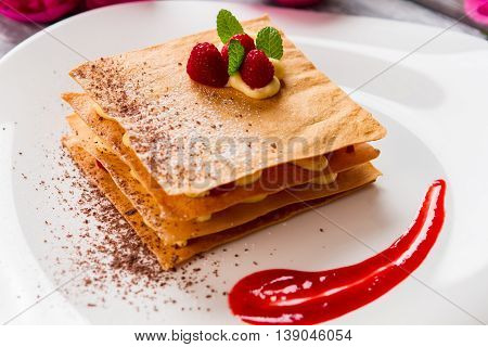 Dessert with sauce on plate. Raspberries and mint leaves. Sweet taste of millefeuille. Crispy pastry with custard.