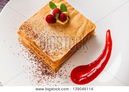 Dessert with raspberries. Brown powder and mint. Pastry with chocolate crumbs. Top view of millefeuille.