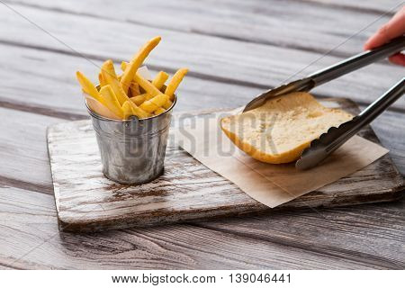Fries in small bucket. Tongs hold toast bread. Let's make a sandwich. Crispy french fries in cafe.