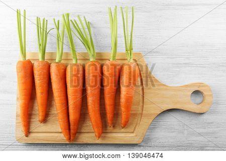 Fresh carrots on wooden cutting board