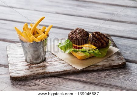 French fries near bread slice. Grilled meat and cheese. How to make a burger. High-calorie meal.