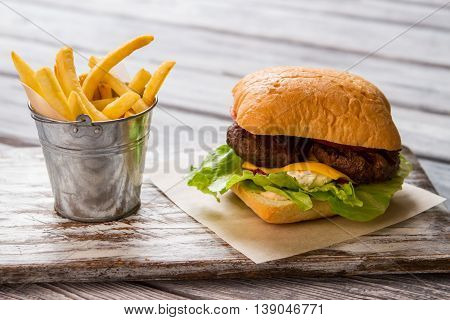 Bucket of fries near burger. Lettuce and grilled meat. Snack in local bistro. Freshly cooked cheeseburger.