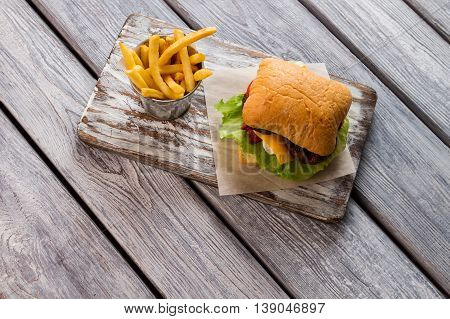 Fries and burger on board. Buns and lettuce leaves. Example of fast food dishes. Secret recipe of cheeseburger.
