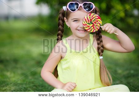 Little girl, brunette with long hair braided in two pigtails, in the ears of gold earrings, wearing sun glasses in a pink frame with glass in the shape of hearts, wearing a yellow T-shirt and pants, sitting on green grass in the summer park with a large r