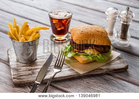 Hamburger and fries. Glass of cola and spices. Fast food in american diner. Juicy beef and warm cheese.