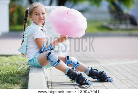 Blonde little girl with two long pigtails wearing a white t-shirt and blue shorts,wearing knee pads and protection on elbows blue,spends time alone in a city Park, roller skating black and blue in the summer,eat a sweet pink cotton candy