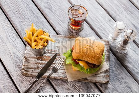 Bucket of fries and hamburger. Knife with fork on board. Example of unhealthy food. Beefburger and cola.