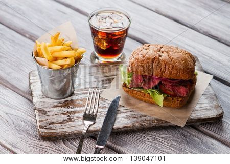 Bucket of fries and sandwich. Drink with ice. Savoury meal in american diner. Tasty sandwich with cooked veal.