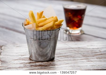 Small bucket with yellow fries. Glass with drink in background. Typical fast food product. High amount of fat.