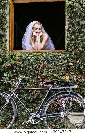 Bride looking out of a window wearing a veil