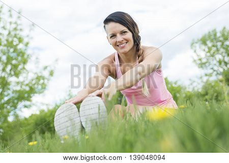 A Young female athlete excercising and stretching in a park