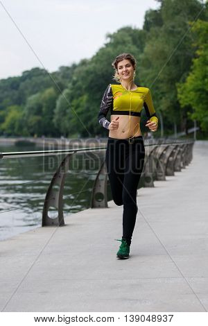 Portrait of athlete woman training outdoors with mp3 player. Symbol of success and endurance in sport.