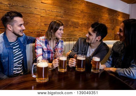 Happy friends with beer mugs at table in restaurant