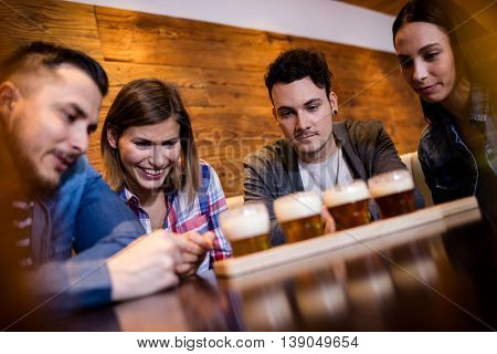 Happy friends looking at beer glasses in restaurant