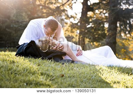 Couple kissing in a park on the grass