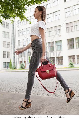 fashion style portrait of young trendy girl walking along the street. Woman with red bag in hand.