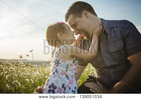 A happy joyful father with daughter on sunset
