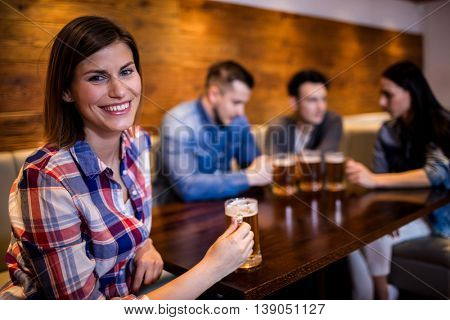 Portrait of smiling woman holding beer mug while friends in background at bar