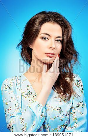 Portrait of casual young woman over blue background. Studio shot.