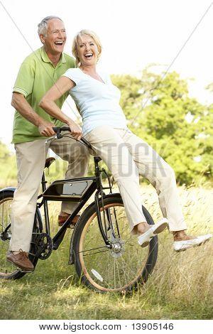 mündig paar reiten Fahrrad in Landschaft
