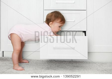 Little child playing with drawer