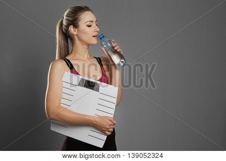 Beautiful young woman holding floor scales on gray background