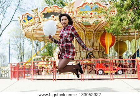 Young woman. Street photo of beautiful woman with candy cotton in the park. Lifestyle photo.