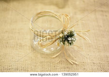 glass bowl with flax yarn and flowers on brown cloth
