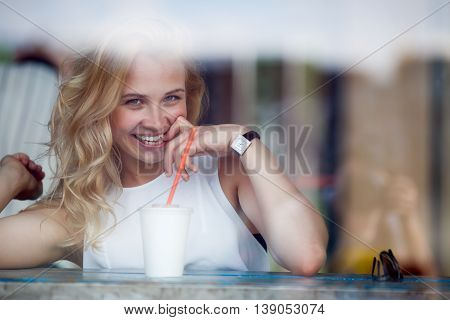 Portrait of attractive flirting blonde girl in cafe. Model sitting with drink, smiling and looking at camera
