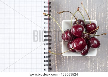 Bowl of fresh cherries and blank notebook for recording