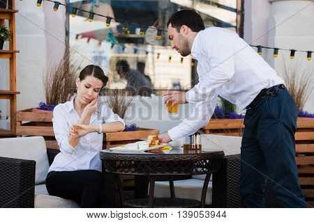 Waiter server at table working reading menu specials list for woman.