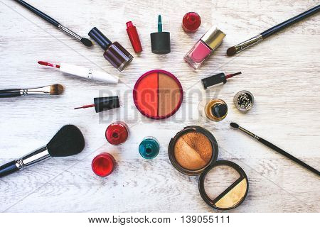 Various cosmetics are laid out on a white wooden table