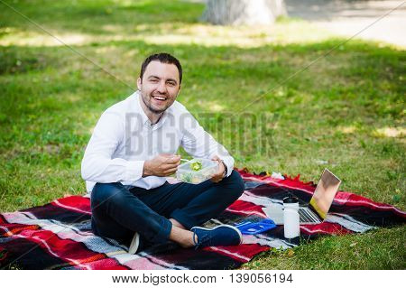 young business man enjoying food which he brought in a lunch box from home. Lunchtime at the park outdoors